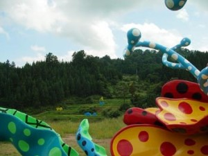"Yayoi Kusama, ""Blooming in Tsumari"" (part) 2003, fiberglass and paint (Ilya and Emilia Kabakov's ""The Rice Field"" is in the background)"